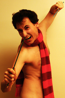 man wearing nothing but a scarf, wielding knitting needles like weapons in a comedic fashion