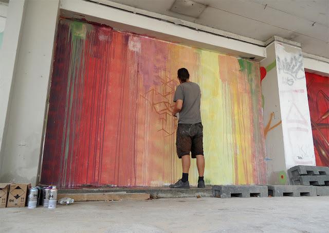 etnik working on a new street art mural in paris