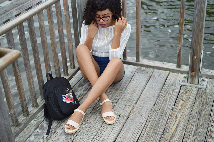 indie fashion blogger anais alexandre of down to stars in a sheer white striped top and high waisted jean shorts with nude jelly sandals on a dock