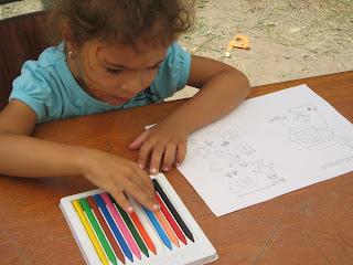 Pillangó-arcú (festett) ülő leányka válogatja az asztalon levő zsírkréták közül a számára megfelelő színt.