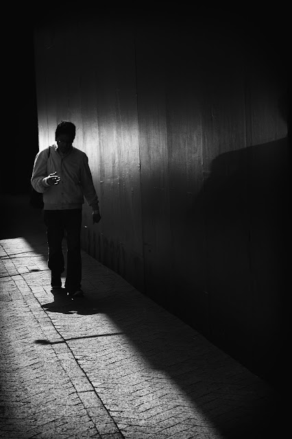 A man walks silhouetted by light