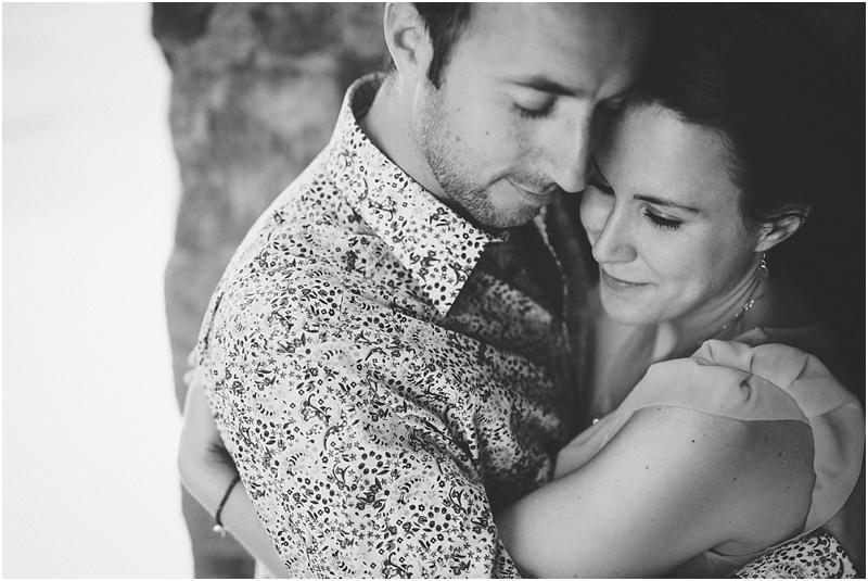 A black & white photo of a couple cuddling at Glastonbury Tor