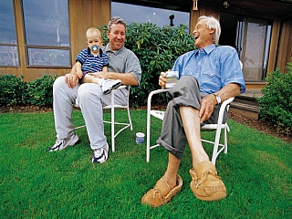 A father and son having a lively conversation with a elderly parent outdoors