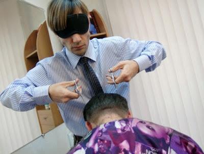 Pekerja gunting rambut dengan mata tertutup