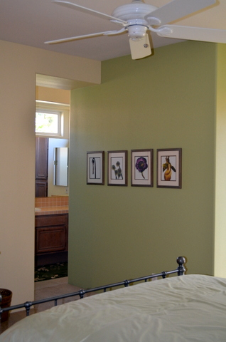 Bedroom wall with prints against Watercress paint