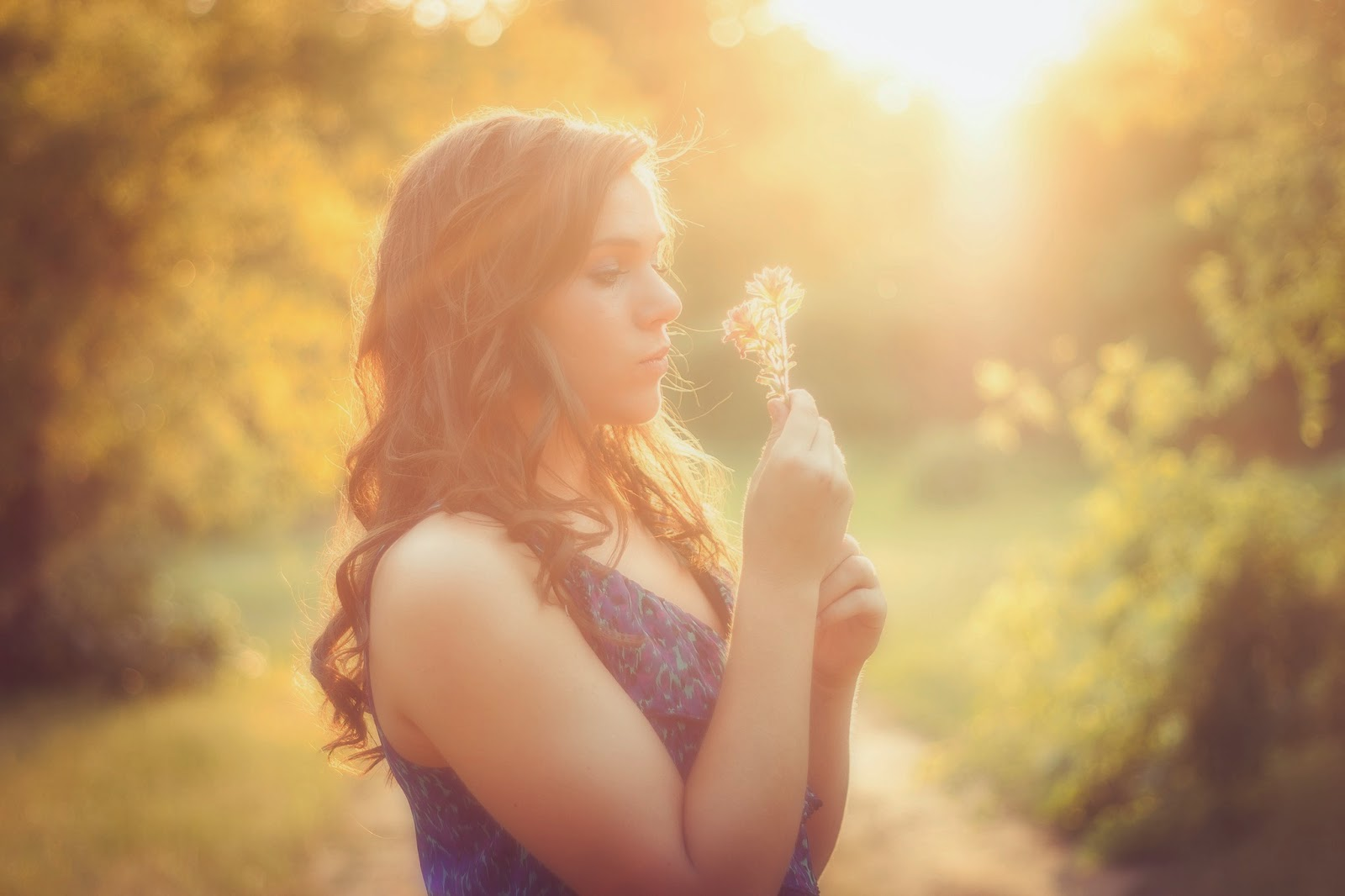 Girl looking at flowers at sunset