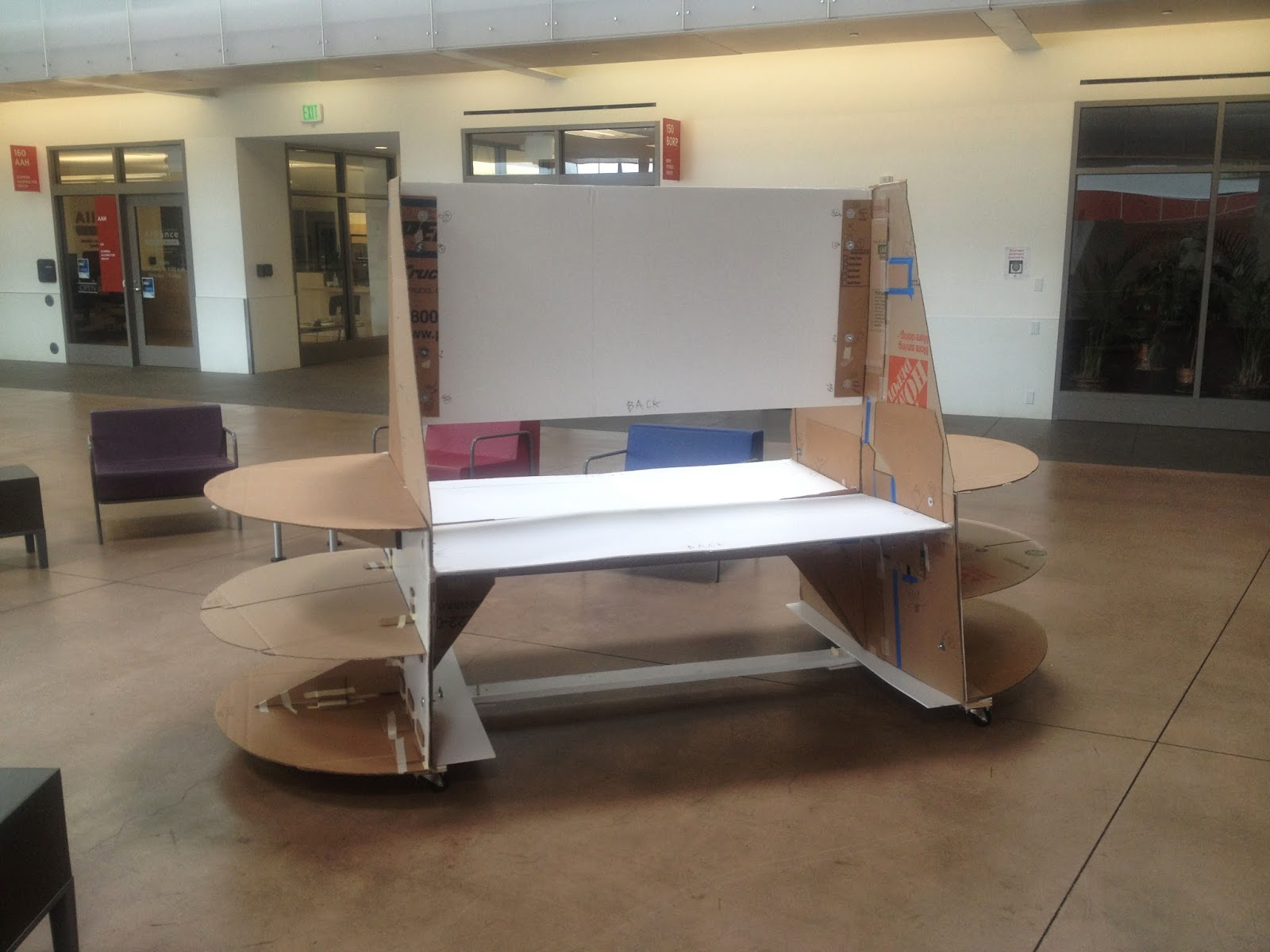 The cardboard model is completely assembled with the dolly attached underneath. It is standing within the Ed Roberts Building within the lounge area.