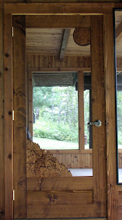 hand carved cedar screen door, hand carved wolf howling,  built by john huisman, ely, mn