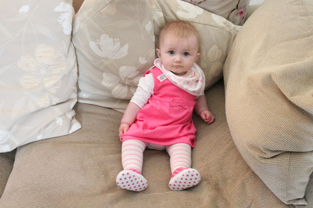 baby wearing bright pink dress with long sleeved white vest, pink trainers and pale pink tights