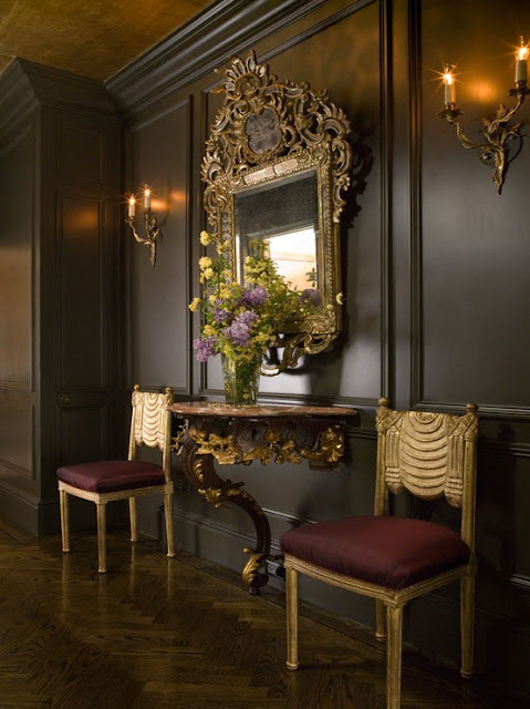 chocolate black walls ornate gold mirror hallway