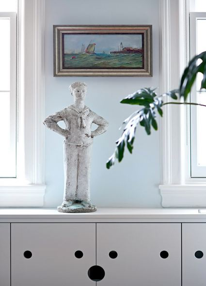 concrete sailor satatue sitting on top of a light gray cabinet with finger holes to open