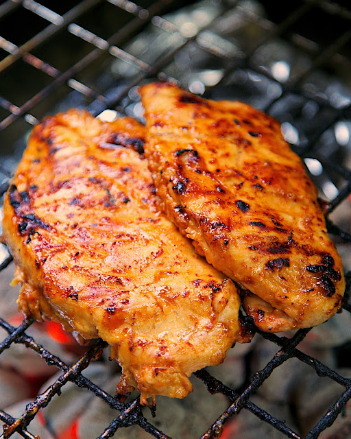 Orange Sriracha Grilled Chicken Recipe - chicken marinated in bbq sauce, mustard, Sriracha, honey and orange juice. Sweet, smokey and a tad bit spicy. SO good! Tons of great flavor and super juicy. We doubled the recipe for leftovers.
