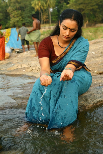 Shwetha Menon in saree in river bending down sexy pic