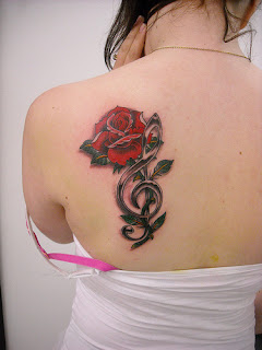 Red Rose Tattoo with Musical Notes Design on Girls Upper back