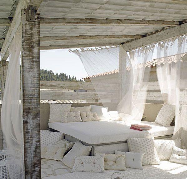 en la imagen zona chill out muy apetecible conseguida con una estructura de obra recubierta de una colchoneta tapizada en crudo y muchos