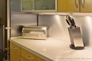 Glatte Nischenverkleidung in Alu - Optik statt Fliesenspiegel gibt der Küche einen modernen, freundlichen Charakter