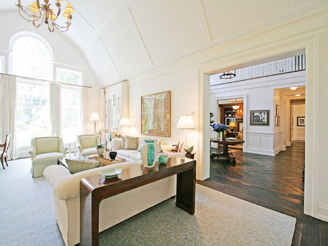 Livng room with high white gambrell ceilings, a fireplace, traditional decor and a view to foyer