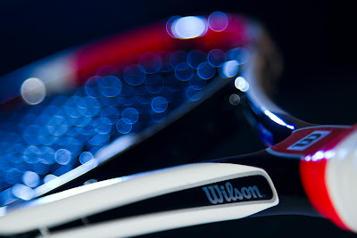 A Photograph of a Tennis racquet with blue bokeh created on the strings.