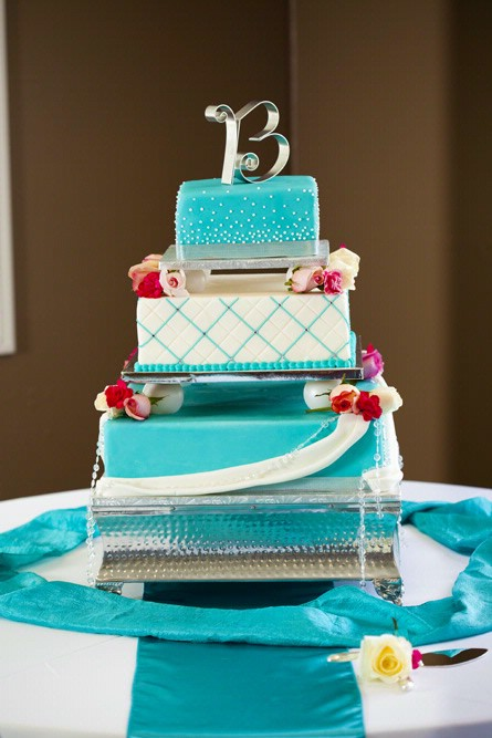 square turquoise and white cake with red flower accents