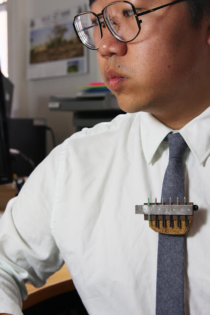 Man in office wearing a brooch made from biros and pin board.
