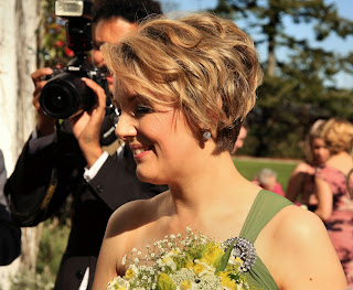 Bridesmaid with short blonde hair, wearing a green dress