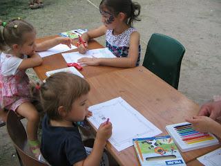 Három copfos óvódás lányka az első jelentkezők asztalomnál. Az asztalok itt még sorban vannak, később összetoltam őket. Rajtuk játszólapok, színesceruzák vannak.