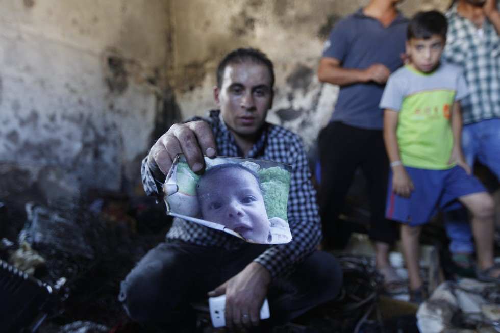 70 Of The Most Touching Photos Taken In 2015 - A relative holds a photo of 18-month-old Ali Dawabsheh. He was killed when suspected Jewish extremists threw firebombs into his family's home.