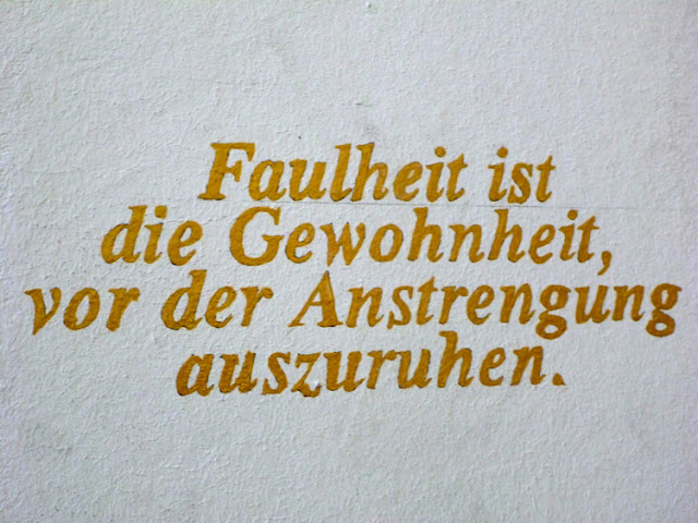 Wandinschrift: Faulheit ist die Gewohnheit, vor der Anstrengung auszuruhen.