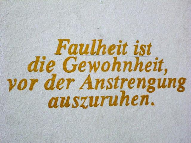 Wandinschrift: Faulheit ist die Gewohnheit, vor der Anstrengung auszuruhen.
