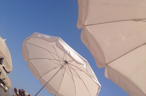 White parasols in the bright blue Riviera sky.