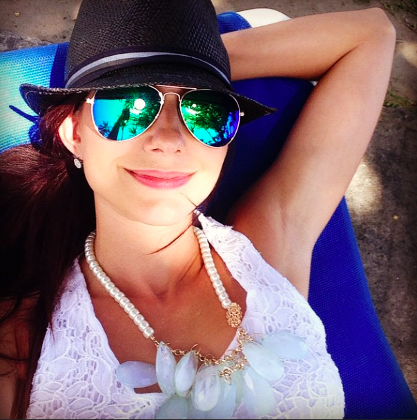 Amy West in a fedora and aviators.