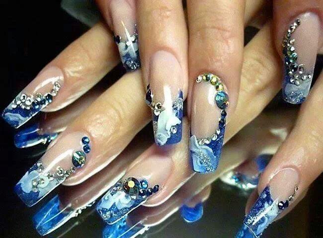 Uñas decoradas largas con un french azul y un diseño blanco, estas uñas son muy llamativas ya que contiene unos diamantes grandes y pequeños azules.