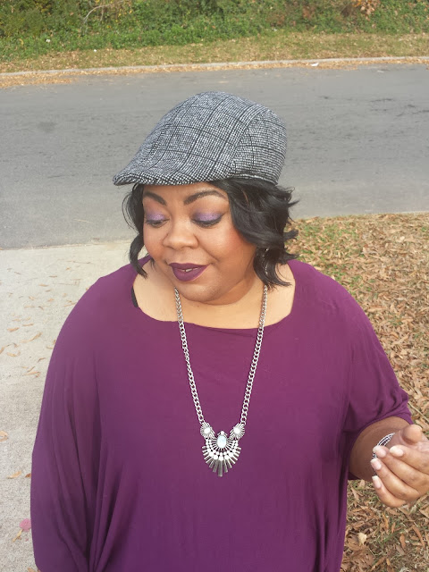 purple poncho with black jeans and fashion hat