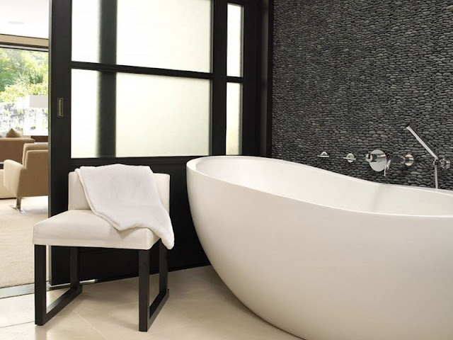 Black bathroom in the Aspen Residence by Stonefox with white bath tub and a single black chair