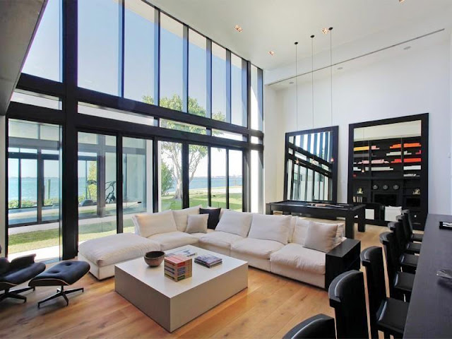 game room with wood floors, a white L shaped chair, two large black mirrors, and a square block coffee table. Instead of a traditional wall, they have a large glass wall with black panelling