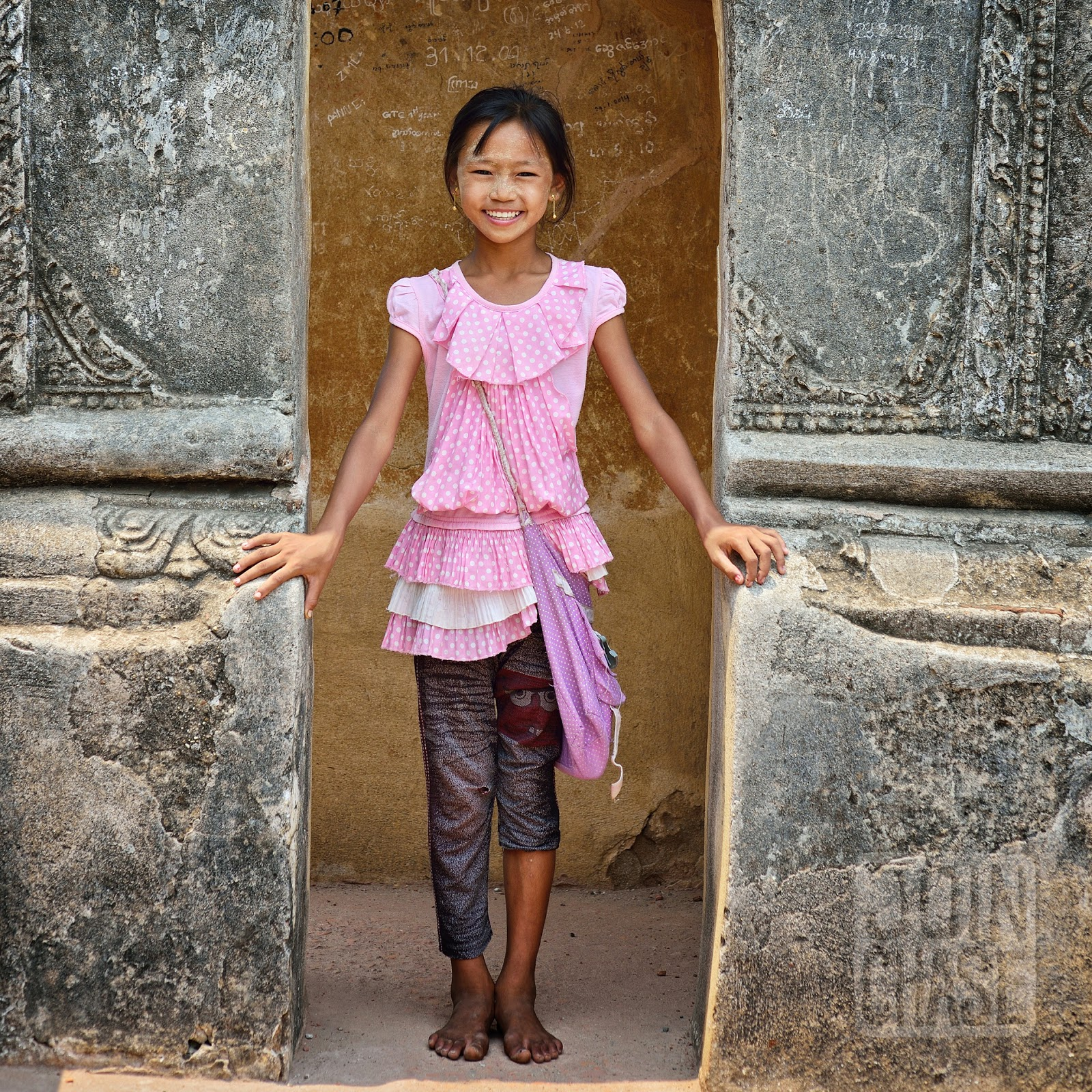 A smiling girl under an arch on top of Shwegugyi Temple in Bagan, Myanmar.