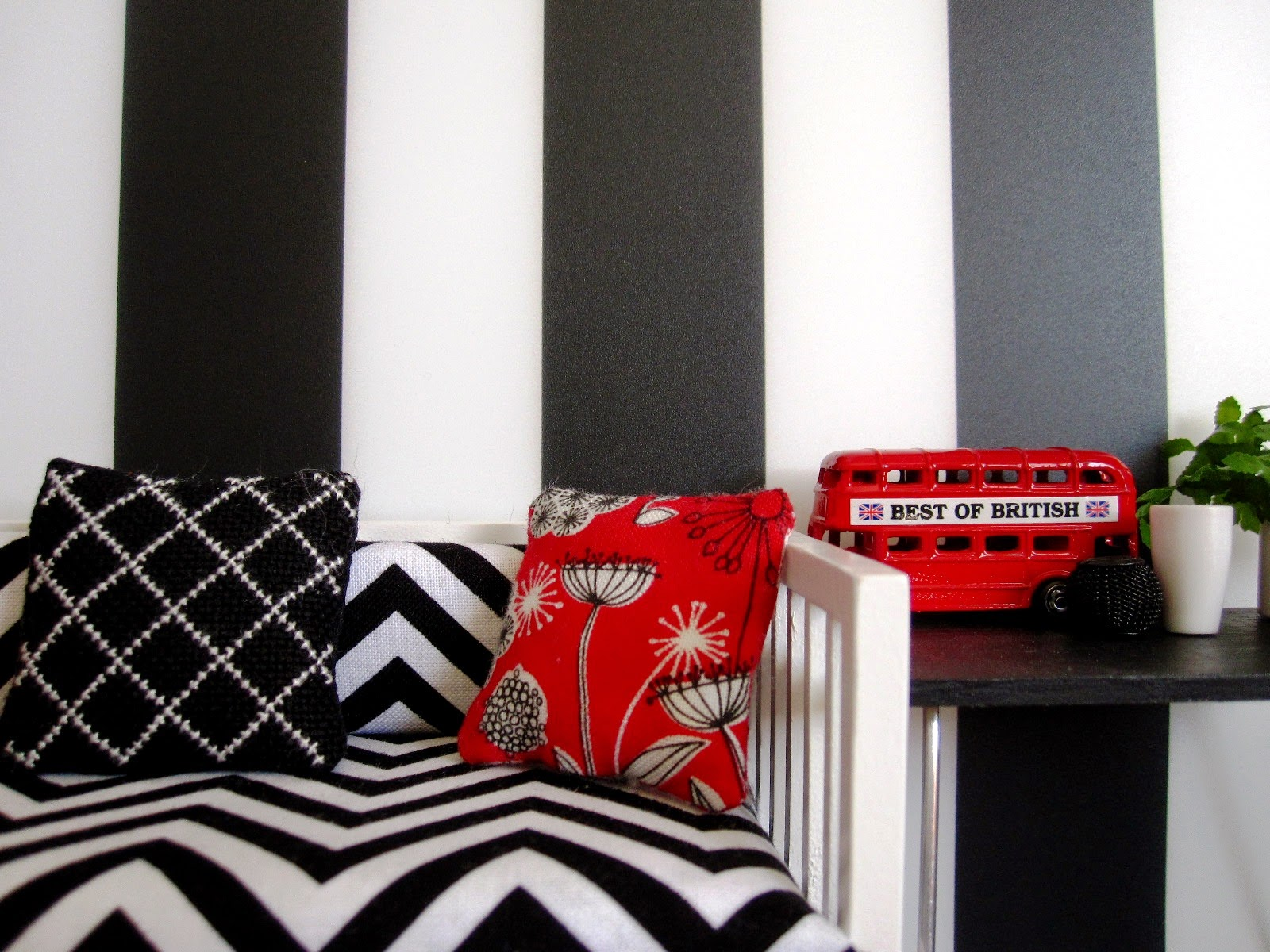Modern miniature black white and red scene of a day bed with cushions next to a table displaying a model London bus and vases.