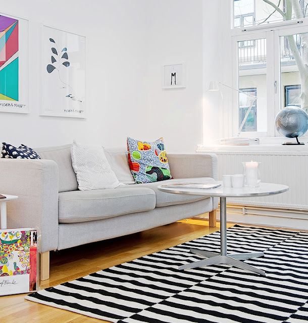 Living room in an apartment with a grey sofa, wood floors and a black and white striped rug and a round metal coffee table