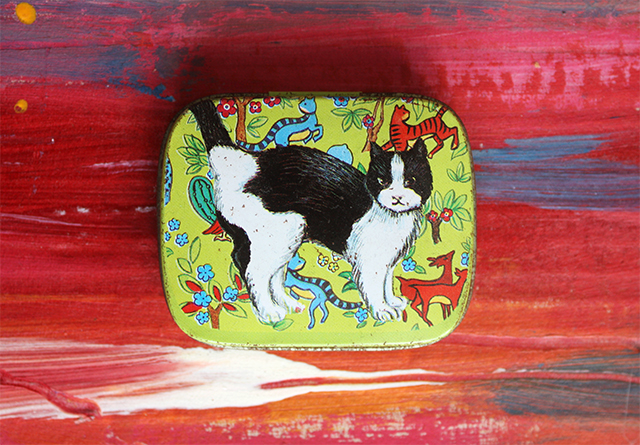 small cat tin with pattern on abstract painted background
