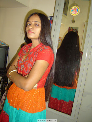 Homely looking south Indian college girl before her home dressing table.