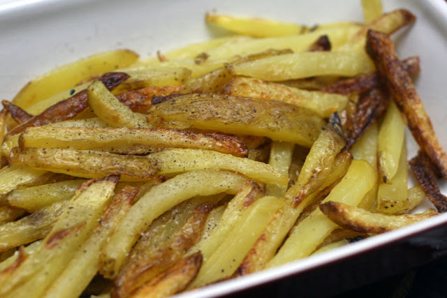 Oven-baked fries with salt and pepper sprinkled over them.