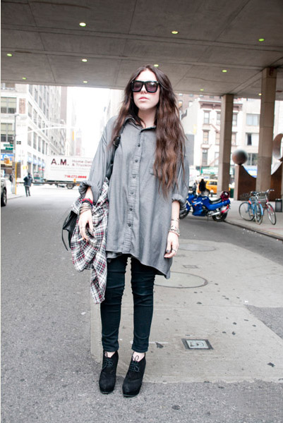 FIT student Jenna Coyle wears a long asymmetrical grey button up shirt over black skinny jeans and wears a pair of suede lace-up heels.