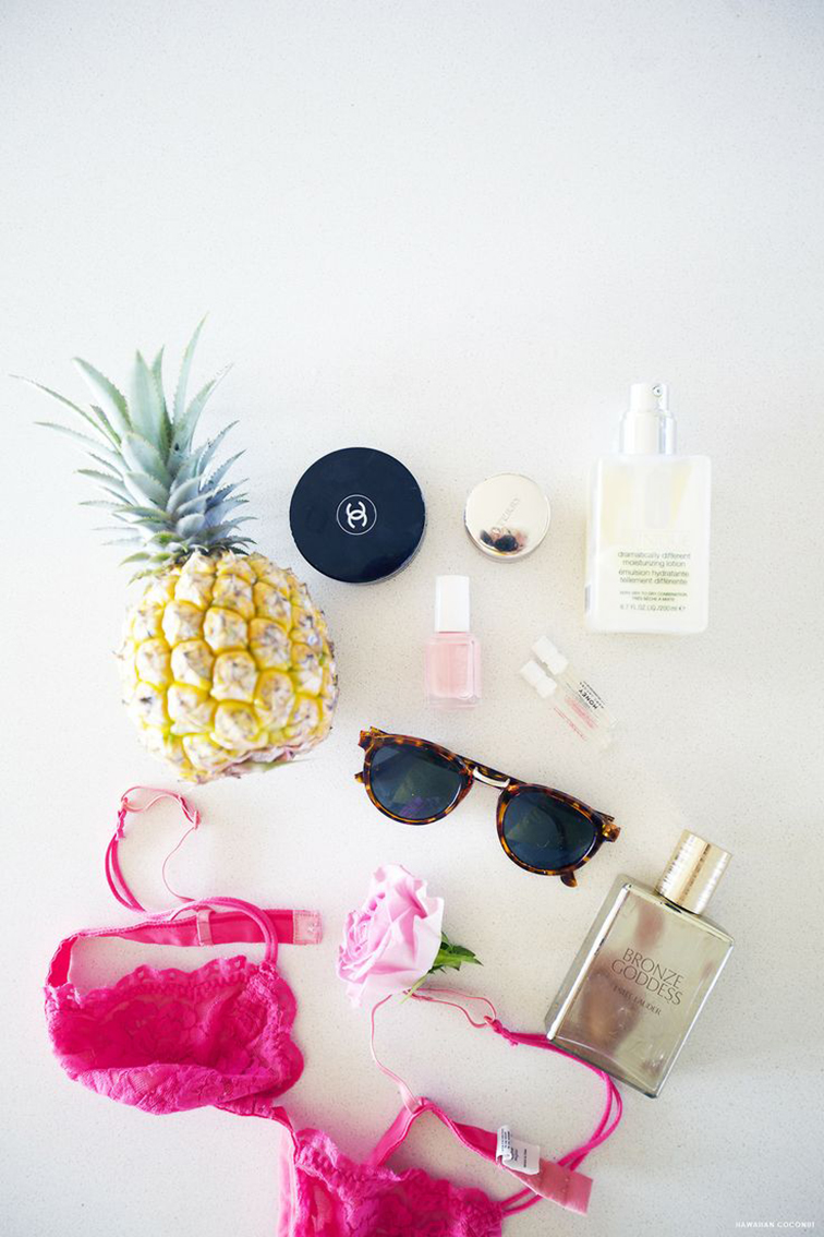 Summer beauty essentials, Chanel makeup compact, Estée Lauder Bronze Goddess, tortoiseshell sunglasses, pink bra, Essie nail polish, whole pineapple