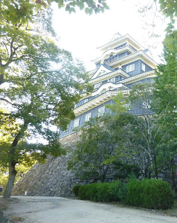 Okayama Castle as seen from the base. It is an impressive black castle with white eves and gold gilding on pointy bits on the top
