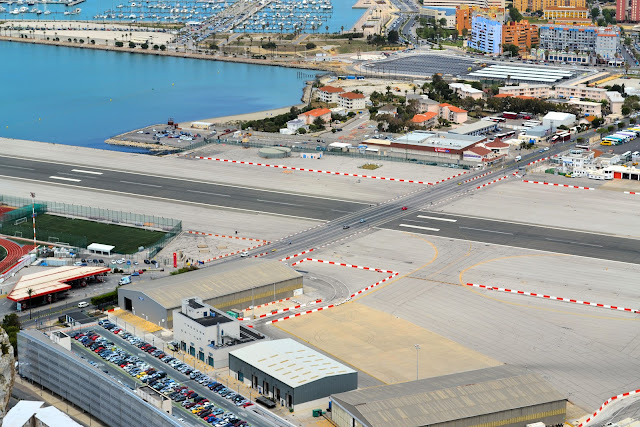 Close-up view showing cars crossing the runway at the Gibratar airport.