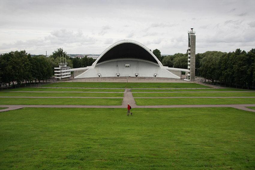 Campo relvado destinado à assistência e ao fundo a zona do palco onde se realizam os concertos e actuações. Um homem a atravessar o campo