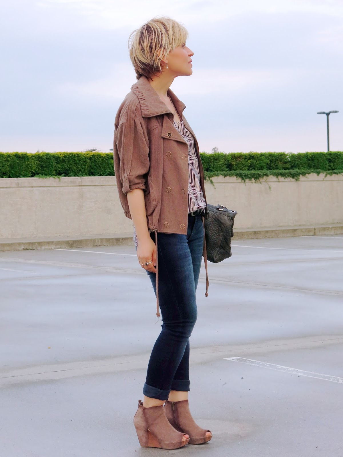 styling skinny jeans with a striped tank, wedge booties, and a khaki bomber jacket