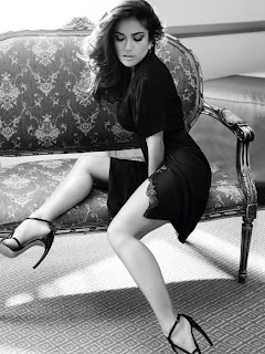 Salma Hayek looks beautiful in a black outfit sitting on a sofa