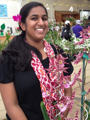 Nilofer Chollampat, smiling with orchid in her hair, standing in front of an orchid plant, holding a laptop