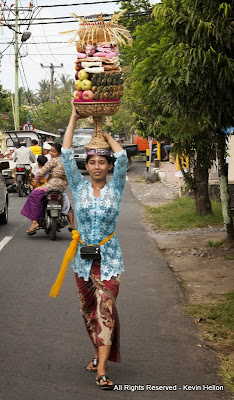 A woman carries a basket of fruit to the temple  during the Galungan festival, Bali